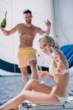 selective focus of smiling woman showing glass of champagne and her boyfriend standing behind on yacht