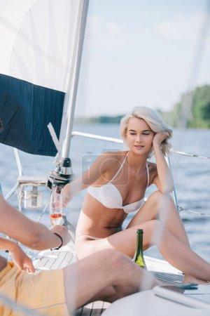 Foto de Imagen recortada de hombre y novia en traje de baño tintineo por copas de champán en el yate - Imagen libre de derechos