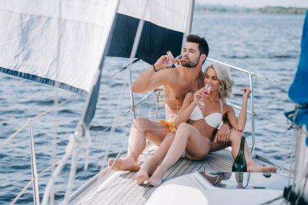 Photo for Smiling couple in swimwear drinking champagne on yacht - Royalty Free Image