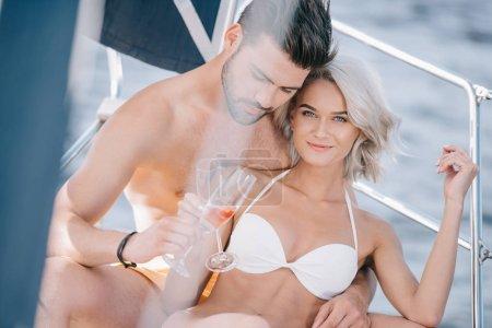 Photo pour Jeune couple en maillot de bain cliquetis de verres de champagne sur l'yacht - image libre de droit