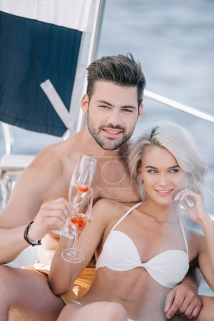 smiling young couple in swimwear relaxing with champagne glasses on yacht
