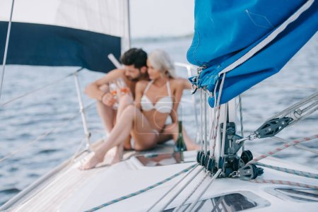 selective focus of sail and couple in swimwear relaxing with champagne glasses behind on yacht