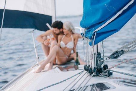 Photo pour Mise au point sélective de voile et de couple en maillot de bain relaxant avec les verres de champagne derrière sur yacht - image libre de droit