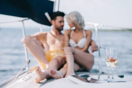 selective focus of champagne glasses and couple sitting behind on yacht