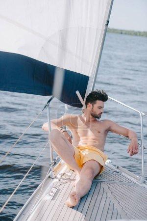 shirtless muscular man in swim trunks having sunbath on yacht