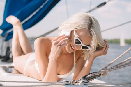 smiling attractive woman in sunglasses and bikini talking on smartphone and laying on yacht