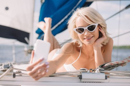 smiling attractive woman in bikini and sunglasses taking selfie on smartphone while laying on yacht