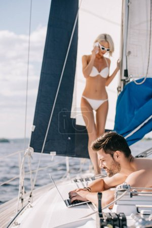 smiling man using laptop and his attractive young girlfriend in bikini talking on smartphone on yacht