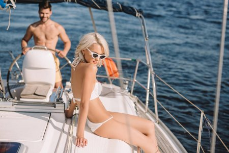 beautiful young woman in bikini having sunbath while her boyfriend steering yacht