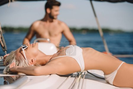 selective focus of attractive young woman in bikini having sunbath while her boyfriend steering yacht