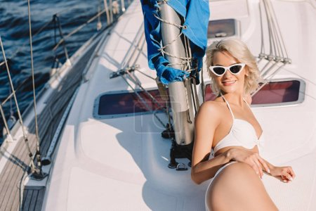 high angle view of young woman in sunglasses and bikini having sunbath on yacht