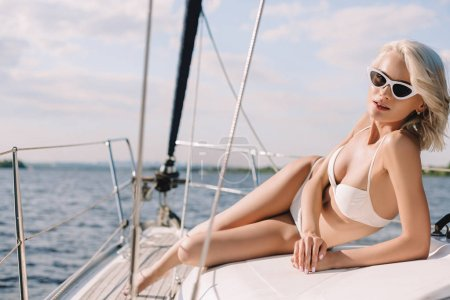 attractive young woman in sunglasses and bikini looking at camera on yacht
