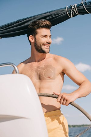 smiling shirtless muscular man in swim trunks steering yacht