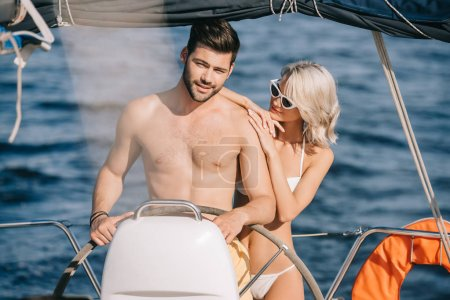 young attractive woman embracing shirtless boyfriend while he steering yacht