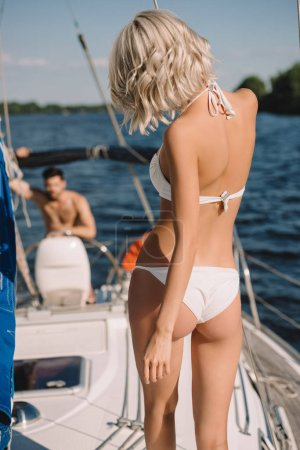 rear view of woman in bikini and her boyfriend standing behind on yacht