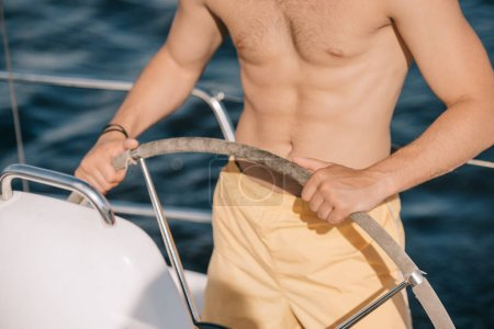 cropped image of shirtless muscular man in swim trunks steering yacht