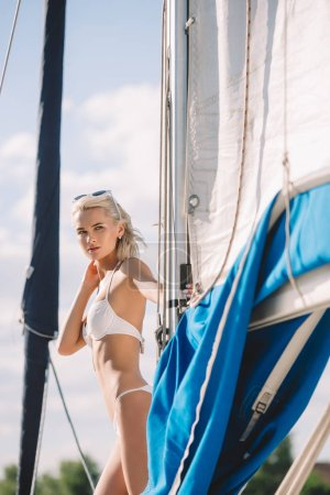 beautiful young woman in bikini looking away on yacht