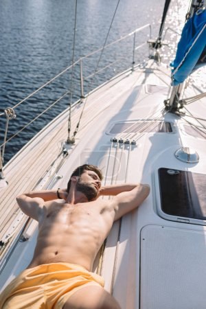 high angle view of shirtless muscular man in swim trunks having sunbath on yacht