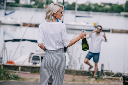 selective focus of young woman with bottle of champagne and her boyfriend behind on blurred background