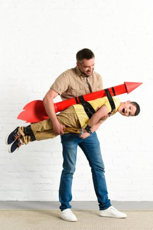 father holding son with toy rocket on back at home