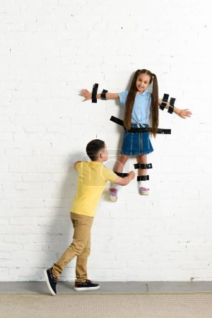 brother gluing sister to wall with black tape at home