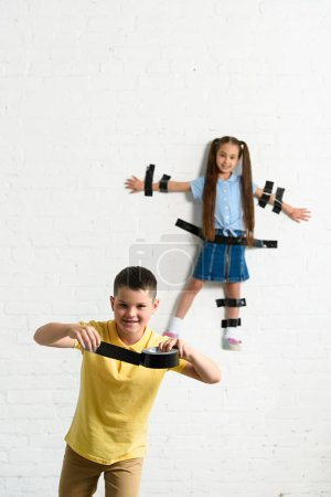 disobedient brother glued sister to wall with black tape at home