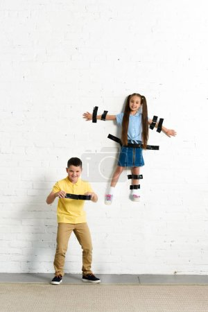 brother glued sister to wall with black tape at home