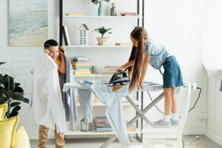 disobedient siblings ironing clothes at home