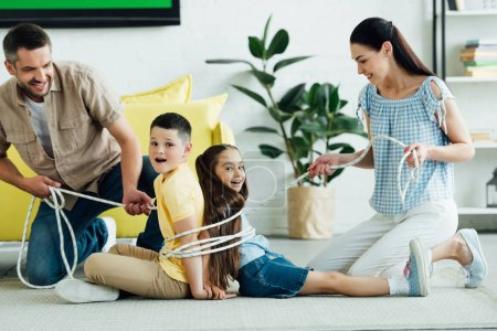 smiling parents tying children with rope at home, parenthood concept