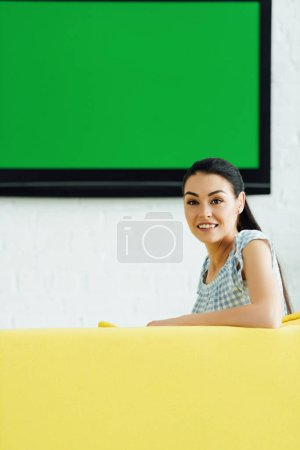 attractive woman sitting on yellow sofa at home and looking at camera