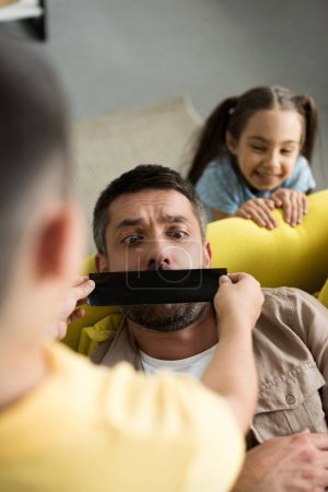 overhead view of children closing father mouth with black tape at home