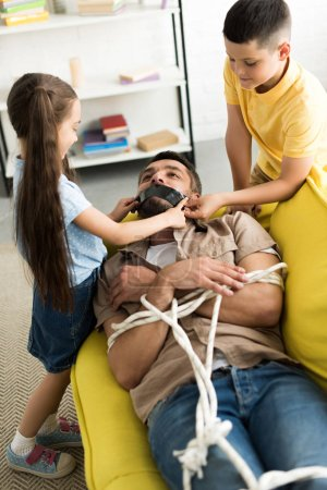 children closing father mouth with black tape at home