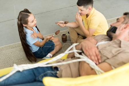 high angle view of children eating chocolate and father lying tied on sofa at home