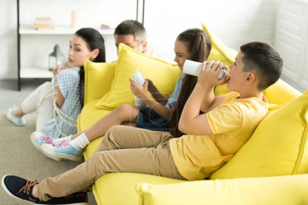 tied parents sitting near sofa and siblings eating sweets at home