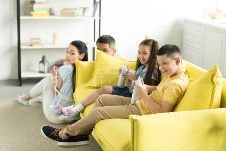 tied parents sitting near sofa and disobedient children eating sweets at home