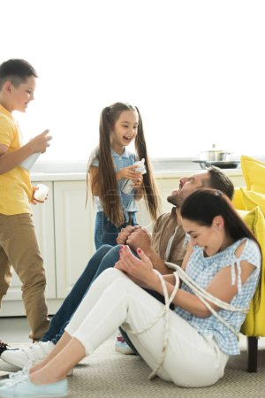 tied parents sitting near sofa and disobedient children scaring them with cream at home
