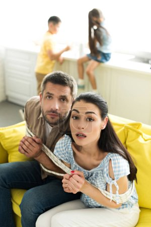 scared tied parents sitting on sofa and looking at camera at home, parenthood concept