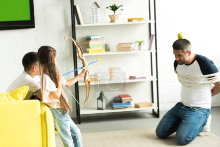 side view of children playing with tied father and pretending shooting with toy bow at home