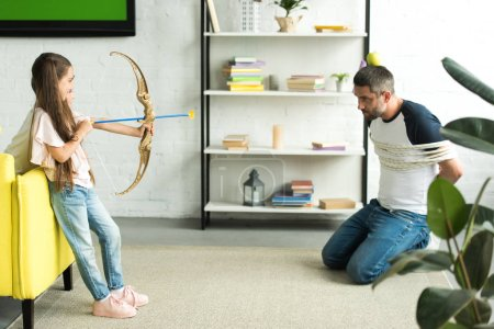 side view of daughter playing with tied father and pretending shooting with toy bow at home