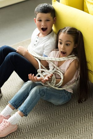 tied with rope sister and brother sitting on floor and screaming at home