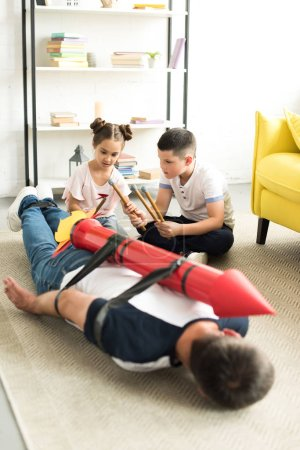 tied dad with rocket toy lying on floor and children playing with him