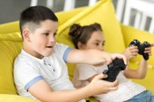 siblings playing video game on sofa at home
