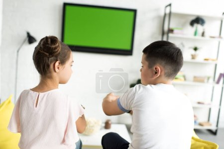 siblings playing video game at home
