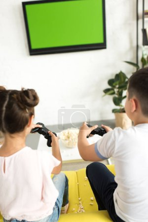 back view of sister and brother playing video game at home