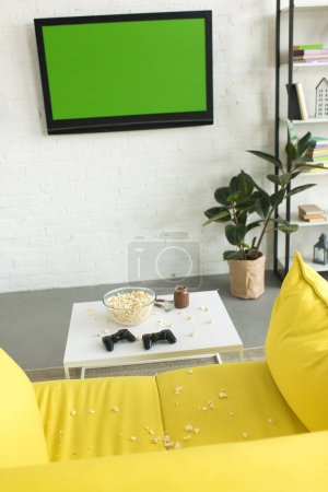 high angle view of glass bowl with popcorn and joysticks on table near yellow sofa in living room