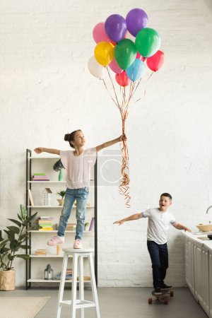 disobedient sister and brother with balloons and skateboard in kitchen