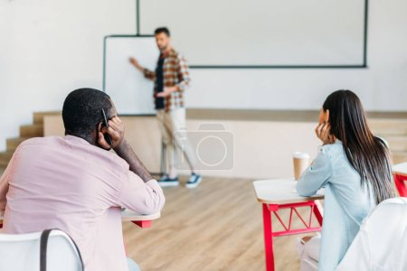 handsome young teacher making presentation for group of students at university