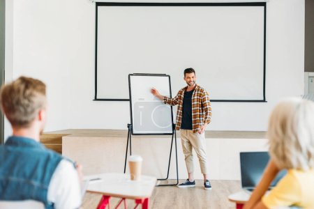 handsome young teacher making presentation for group of students at college