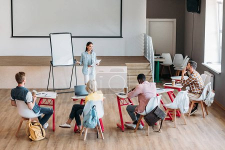Grupo de jóvenes estudiantes en clase y escuchar conferencias