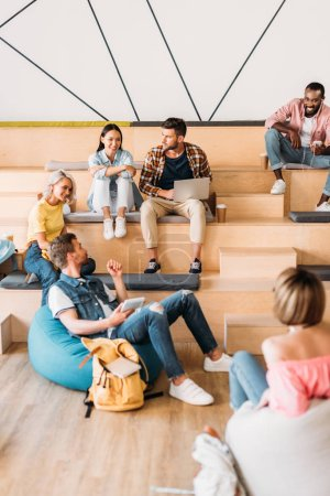 multiethnic young students spending time together at college on wooden tribunes